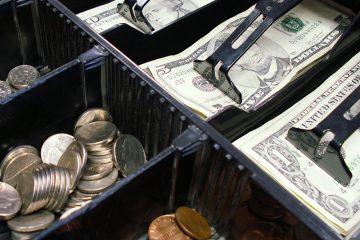 offene Kassenlade mit Geldscheinen und Münzen