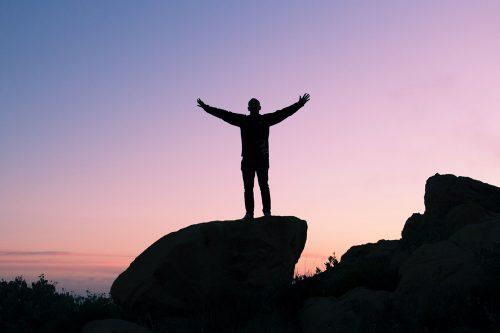 Mann steht auf Fels und breitet die Arme aus während Sonnenuntergang